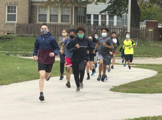 Michelle Davies | The Journal Gazette Lakeside Middle School's cross country intramural group goes through warm-up drills during practice.