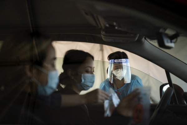 Associated Press A medical worker assists two women with COVID-19 testing Monday atthe Orange County Fairgrounds in Costa Mesa, Calif.
