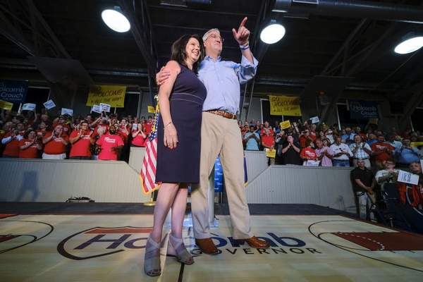 Associated Press: Indiana Gov. Eric Holcomb, right, with his wife, Janet, are seen on stage after Holcomb announced his re-election bid at a campaign rally in Knightstown, Ind., on July 13, 2019. The Holcombs have begun quarantining after several members of his security detail tested positive for COVID-19.