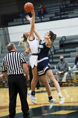 Rachel Bellwood | The Journal Gazette  Bellmont's Morgan Shifferly and Bishop Dwenger's Maggie Cheever battle for the ball at the tip-off of their girls basketball gameatBellmont on Tuesday.