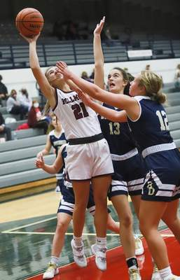 Rachel Bellwood | The Journal Gazette Bellmont's Faith Morris takes a shot against two Bishop Dwenger defenders during the first quarterofTuesday night's game atBellmont.