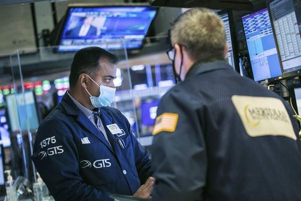 In this photo, provided by the New York Stock Exchange, specialist Dilip Patel, left, works with a trader on the floor of the NYSE, Thursday, Nov. 19, 2020. (Courtney Crow/New York Stock Exchange via AP)