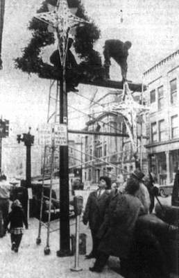 Representatives of the Retail Merchants Division of the Chamber of Commerce, which provided the downtown Christmas decorations, watch workmen put the finishing touches on a light pole arrangement in November 1954. (Journal Gazette file photo)