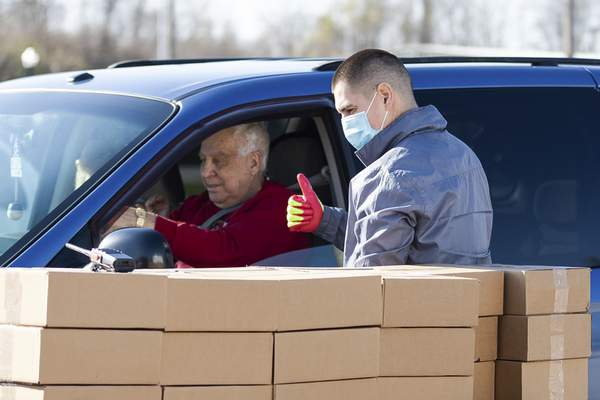 Rachel Bellwood | The Journal Gazette Volunteer John Nix hands out food during Friday's community Grab N' Go, hosted by Aging & In-Home Services. The agency  handed out meals to people 60 and older at the  Parkview Field Silver Lot. Each attendee was given 10 meals.