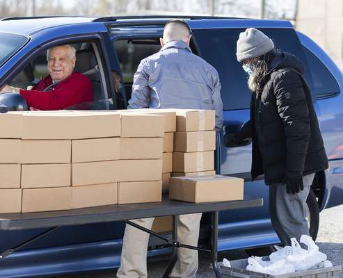 Rachel Bellwood | The Journal Gazette  Volunteers John Nix and Jay Arias follow social distancing guidelines as they load meals into a vehicle. The community Grab N' Go hosted by Aging & In-Home Services handed out meals to seniors 60 and older at the TinCaps Parkview Field Silver Lot on Friday. Each attendee was given 10 meals.