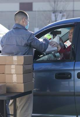 Rachel Bellwood | The Journal Gazette  Volunteer John Nix hands out foodfor theGrab N' Go event hosted by Aging & In-Home Services on Friday. Each attendee was given 10 meals.
