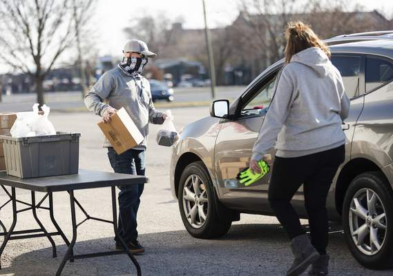 Rachel Bellwood | The Journal Gazette  Volunteers Mark Terry May and Steph May work to load cars for the Grab N' Go hosted by Aging & In-Home Services on Friday. Each attendee was given 10 meals.