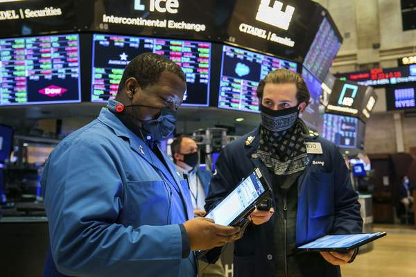 In this photo provided by the New York Stock Exchange, traders Thomas Lee, left, and Benjamin Tuchman work on the floor Friday, Nov. 20, 2020. U.S. stocks are pulling a bit lower in midday trading Friday as worries about the worsening pandemic weigh on rising optimism about a coming coronavirus vaccine. (Courtney Crow/New York Stock Exchange via AP)