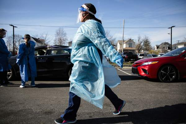 A nurse carries a COVID-19 test back for processing on Thursday, Nov. 19, 2020 at PrimaryOne Health in Columbus, Ohio. The testing site, a pop-up site staffed by medics from the Ohio National Guard and PrimaryOne Health employees, had lines that stretched for a half-mile from the testing site, with wait times for patients up to two hours or more. (Joshua A. Bickel /The Columbus Dispatch via AP)