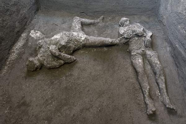 The casts of what are believed to have been a rich man and his male slave fleeing the volcanic eruption of Vesuvius nearly 2,000 years ago. (Parco Archeologico di Pompei via AP)