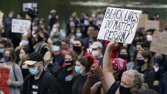 In this Sept. 29, 2020, file photo, a man holds a sign during a protest, in Cleveland. (AP Photo/Tony Dejak, File)