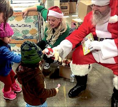 Photo courtesy Jama Smith Santa and helper Jama Smith pass out gifts donated to the Salvation Army as part of the 2019 campaign.