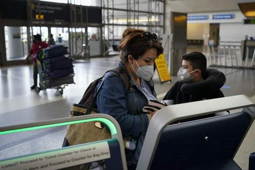 Virus Outbreak California Associated Press Esmeralda Elizalde checks in for her flight Monday to Mexico at the Los Angeles International Airport. About 1 million Americans a day packed airports and planes over the weekend even as coronavirus deaths surged across the U.S.  (Jae C. HongSTF)