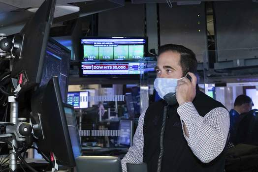 Financial Markets Wall Street Associated Press A trader at the New York Stock Exchange works at his terminal Tuesday as the Dow Jones Industrial Average traded above 30,000 points for the first time ever.  (Nicole PereiraHONS)