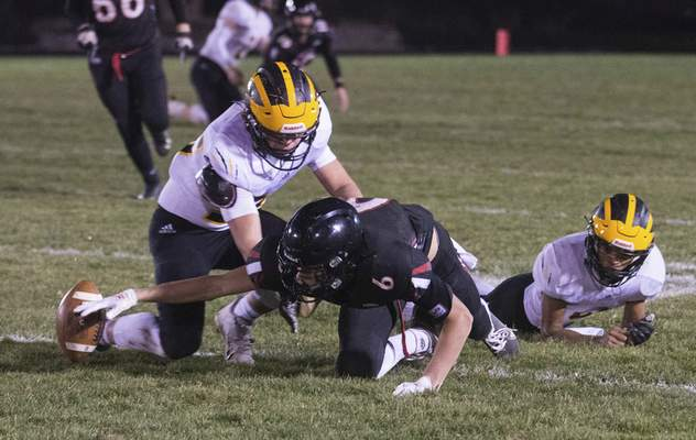 Michelle Davies | The Journal Gazette Bishop Luers' Brody Glenn reaches to regain possession of the ball with Pioneer's Caleb Sweet blocking him in the second quarter of Friday night's game at Bishop Luers.