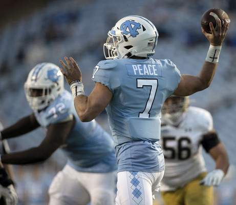 North Carolina quarterback Sam Howell (7), who has the word Peace as his nameplate, throws a pass against Notre Dame during an NCAA college football game, Friday, Nov. 27, 2020, at Kenan Stadium in Chapel Hill, N.C. (Robert Willett/The News & Observer via AP)