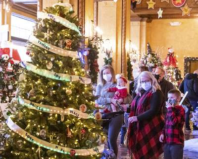 Rachel Bellwood | The Journal Gazette Kiersten Wood with daughter Delaney, son Creigh, and mother Wendy Clark admiring unique and original decorations at the Festival of Trees at the Embassy Theatre on Saturday. (RACHEL BELLWOOD)