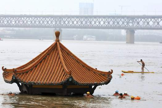 Climate Push Associated Press  In July, residents swim to a riverside pavilion submerged by the flooded Yangtze River in Wuhan, China. An overheating world has seen anextreme year for hurricanes, wildfires, heat waves, floods, droughts and ice melt, the United Nations' weather agency reported Wednesday. (STR)