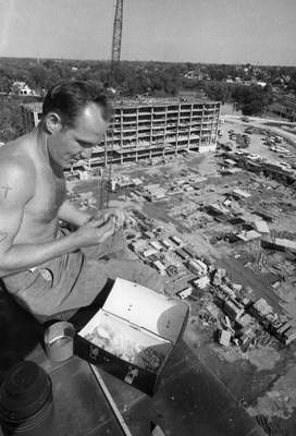 Aug. 17, 1966:Construction worker Robert Walkereats his lunch on what would become the 12th floor of a building in what is now the Three Rivers Apartments complex. (Journal Gazette file photo)
