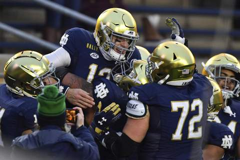 Syracuse Notre Dame Football Notre Dame quarterback Ian Book (12) celebrates after running for a touchdown in the second half of an NCAA college football game Saturday, Dec. 5, 2020, in South Bend, Ind. (Matt Cashore/Pool Photo via AP) (Matt Cashore