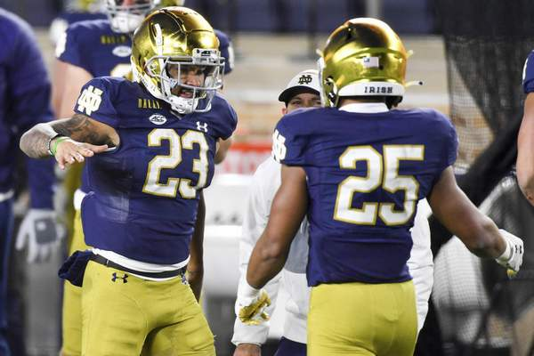 Notre Dame running back Kyren Williams (23) congratulates teammate Chris Tyree (25) after his touchdown against Syracuse in an NCAA college football game Saturday, Dec. 5, 2020, in South Bend, Ind. (Matt Cashore/Pool Photo via AP)