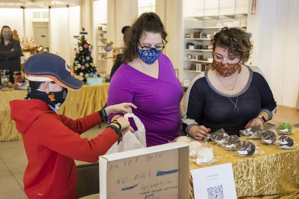 Josh Gales | Journal Gazette Jacob Swick, 10, helps mom Kristen Swick bag up her homemade hot chocolate bombs as Kirsta Hedington, right, organizes the display at the Northeast Indiana Make-A-Wish One-Stop Pop-Up Gift Shop at Jefferson Pointe on Sunday.
