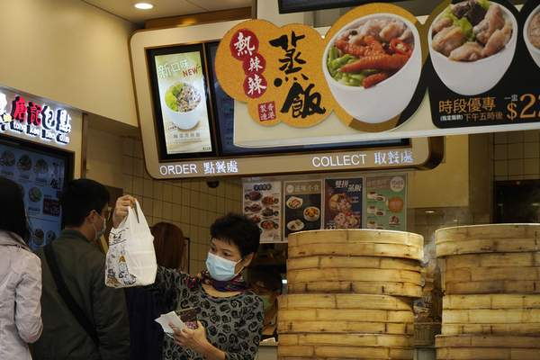 People wearing face masks to protect against the spread of the coronavirus buy their lunch at a food store in Hong Kong, Tuesday, Dec. 8, 2020. (AP Photo/Kin Cheung)