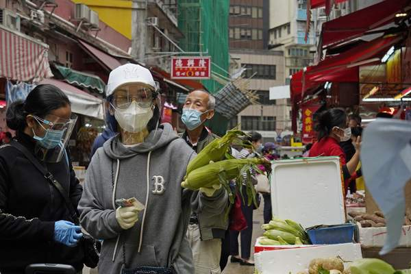 People wearing face masks to protect against the spread of the coronavirus shop at a local market in Hong Kong, Tuesday, Dec. 8, 2020. (AP Photo/Kin Cheung)