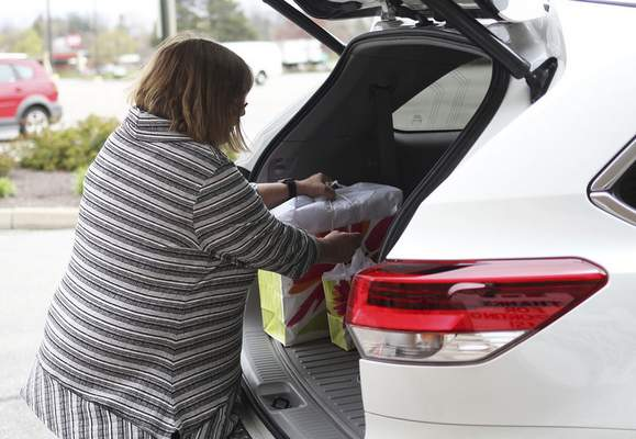 Katie Fyfe | The Journal Gazette In this April photo, Monogram Shoppe owner Sara Keltsch places items for a customer's order in a vehicle. Her store remains open and she also has done Facebook Live promotions to keep the business going during the pandemic.