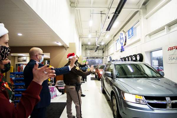 Katie Fyfe | The Journal Gazette Officers wave at families during a toy giveaway hosted by Vorderman Volkswagen partnered with First Responders Children's Foundation based in New York at Vorderman Volkswagen on Saturday morning.