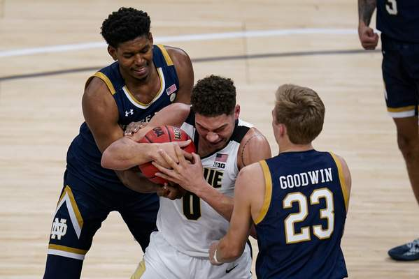 Purdue forward Mason Gillis, center, gets tied up by Notre Dame forward Juwan Durham (11) and guard Dane Goodwin (23) in the second half of an NCAA college basketball game in Indianapolis, Saturday, Dec. 19, 2020. Purdue defeated Notre Dame 88-78. (AP Photo/Michael Conroy)
