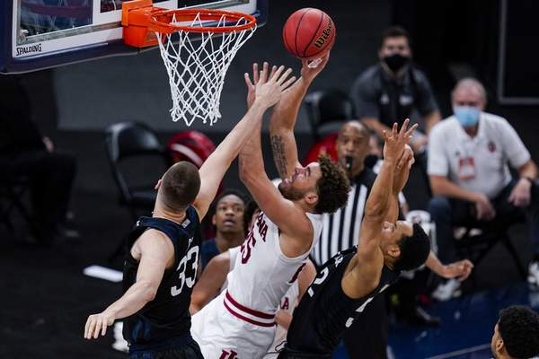 Indiana forward Race Thompson (25) shoots between Butler forward Bryce Golden (33) and guard Jair Bolden (52) in the second half of an NCAA college basketball game in Indianapolis, Saturday, Dec. 19, 2020. (AP Photo/Michael Conroy)