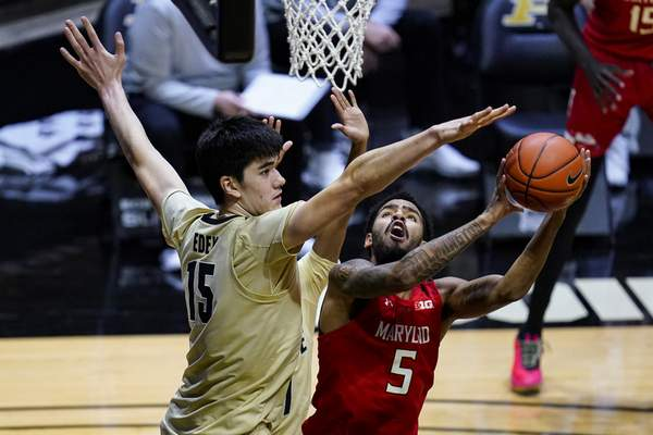 Maryland guard Eric Ayala (5) shoots over Purdue center Zach Edey (15) during the first half of an NCAA college basketball game in West Lafayette, Ind., Friday, Dec. 25, 2020. (AP Photo/Michael Conroy)