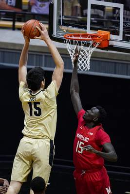 Purdue center Zach Edey (15) goes up for a dunk over Maryland center Chol Marial (15) during the first half of an NCAA college basketball game in West Lafayette, Ind., Friday, Dec. 25, 2020. (AP Photo/Michael Conroy)