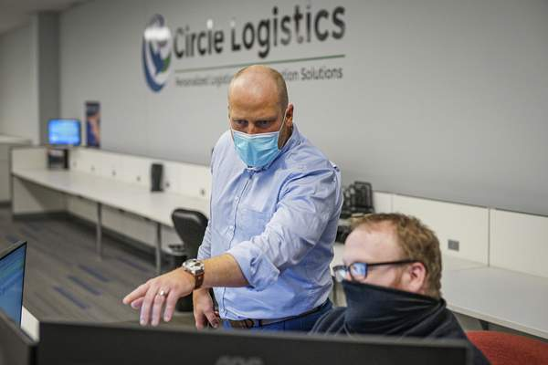 Mike Moore | The Journal Gazette Circle Logistics director of sales T.J. Knudson, left and Alex Root at work in the office l on Friday 12.11.20