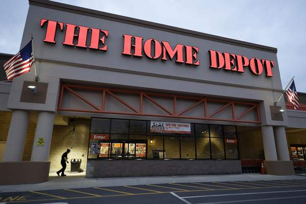 FILE - In this Jan. 27, 2020 file photo a passer-by, below left, walks toward an entrance to a Home Depot store location, in Boston. Home Depot continues to capitalize on the desire of homeowners to improve their houses during the pandemic, with fiscal third-quarter sales surging 23% and beating Wall Street's view. (AP Photo/Steven Senne, File)