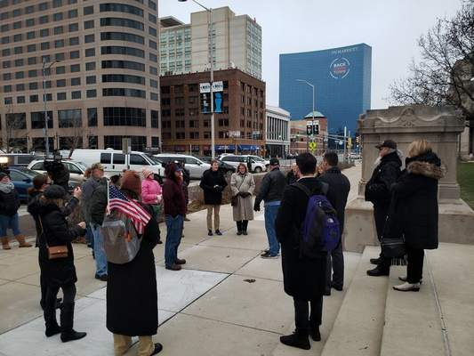 Niki Kelly | The Journal Gazette About 20 people gather around Donald Rainwater on Tuesday in downtown Indianapolis during a protest over Gov. Eric Holcomb's continued public health emergency declarations.