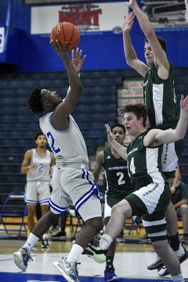 Mike Moore | The Journal Gazette Saint Francis guard Antwaan Cushingberry, left, takes a shot in the first half against Huntington University at the Hutzell Athletic Center on Wednesday.