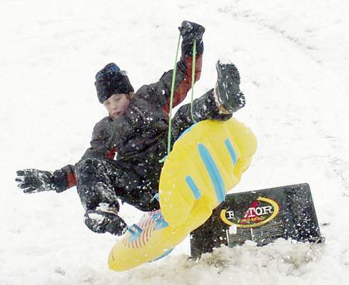 Feb. 20, 2005: Colton Ort, 13, wipes out on the side of a jump while sledding at Franke Park. (Journal Gazette file photo)