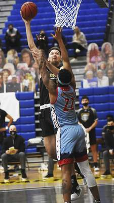 Katie Fyfe | The Journal Gazette  PFW Dylan Carl takes a shot while UIC senior Rob Howard defends him during the second half at the Gates Sports Center on Saturday.