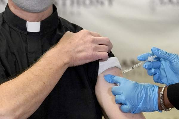 FILE - In this Wednesday, Dec. 23, 2020 file photo, a Catholic pastor receives the first of the two Pfizer-BioNTech COVID-19 vaccinations at a hospital in Chicago. (AP Photo/Charles Rex Arbogast)