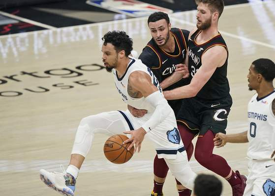 Memphis Grizzlies' Dillon Brooks, left, is fouled by Cleveland Cavaliers' Larry Nance Jr., second from left, in the first half of an NBA basketball game, Monday, Jan. 11, 2021, in Cleveland. Cavaliers' Dean Wade, second from right, and Grizzlies' De'Anthony Melton, right, watch. (AP Photo/Tony Dejak)