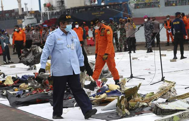 An Indonesian National Transportation Safety Committee (KNKT) investigator inspects the debris found in the waters around the location where Sriwijaya Air passenger jet crashed, at Tanjung Priok Port in Jakarta, Indonesia, Monday, Jan. 11, 2021. (AP Photo/Achmad Ibrahim)
