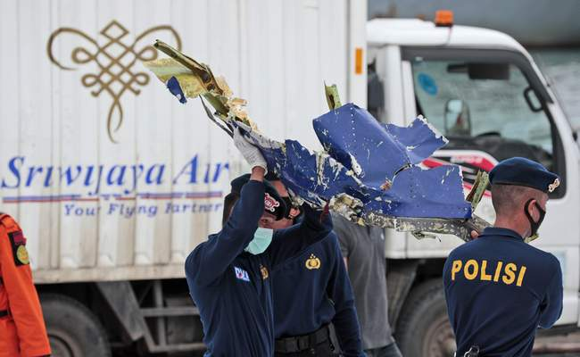 Police officers carry a part of aircraft recovered from Java Sea where a Sriwijaya Air passenger jet crashed, at Tanjung Priok Port in Jakarta, Indonesia, Monday, Jan. 11, 2021. (AP Photo/Dita Alangkara)