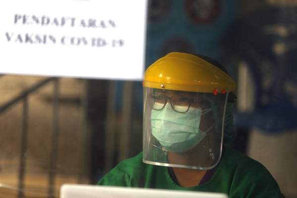 A health worker in a protective suit prepares for coronavirus vaccine drill in Bali, Indonesia on Monday, Jan. 11, 2021. (AP Photo/Firdia Lisnawati)
