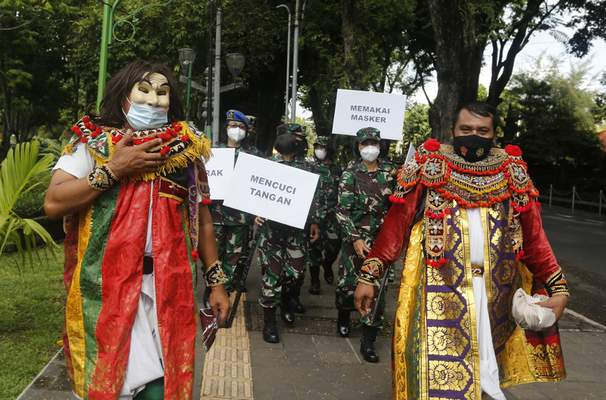 Indonesian military officers wear traditional Balinese costume calling for people to always have their mask and wash hands to prevent the spread of coronavirus outbreak on a street in Bali, Indonesia on Monday, Jan. 11, 2021. (AP Photo/Firdia Lisnawati)