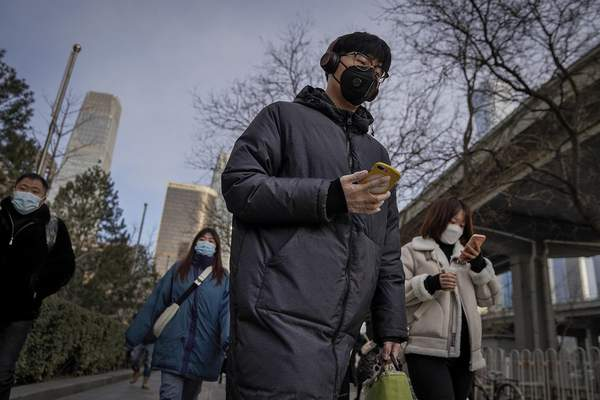 A man wearing a face mask and a disposable gloves to help curb the spread of the coronavirus heads to work with other masked people during the morning rush hour in Beijing, Monday, Jan. 11, 2012. (AP Photo/Andy Wong)