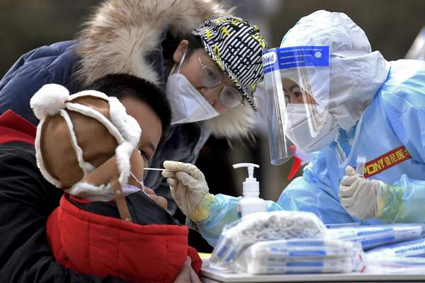 In this photo released by Xinhua News Agency, a medical staff in a protective suit takes a swab from a child near a residential area in Shijiazhuang in northern China's Hebei Province on Sunday, Jan. 10, 2021. (Wang Xiao/Xinhua via AP)