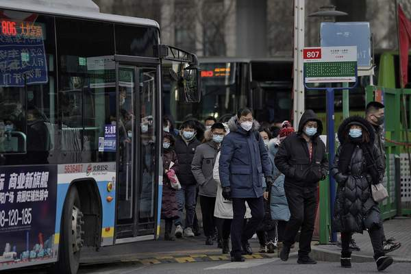 People wearing face masks to help curb the spread of the coronavirus walk out from a bus station for the traveller from the outskirts of Beijing on Monday, Jan. 11, 2012. (AP Photo/Andy Wong)