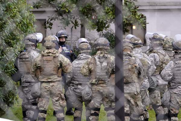 Associated Press A Washington State Patrol trooper talks with members of the Washington National Guard on Monday inside a fence surrounding the Capitol in Olympia, Wash., in anticipation of protests.